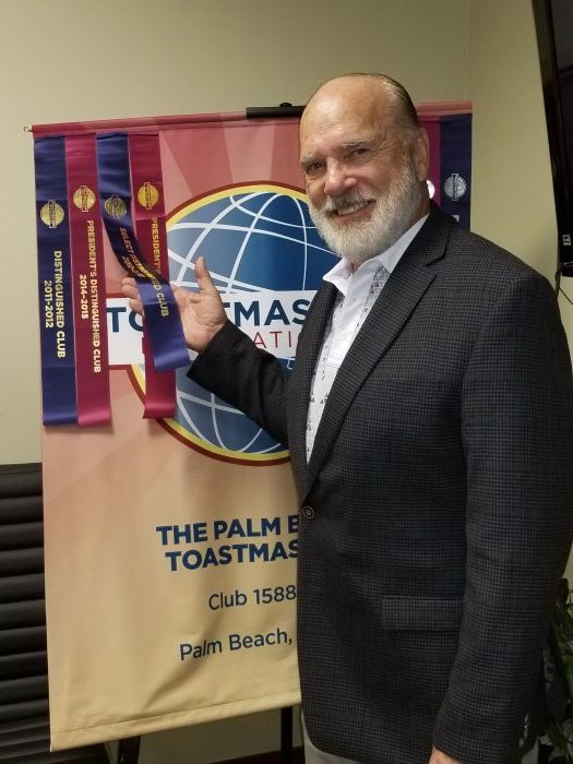 Michael in front of Toastmasters banner
